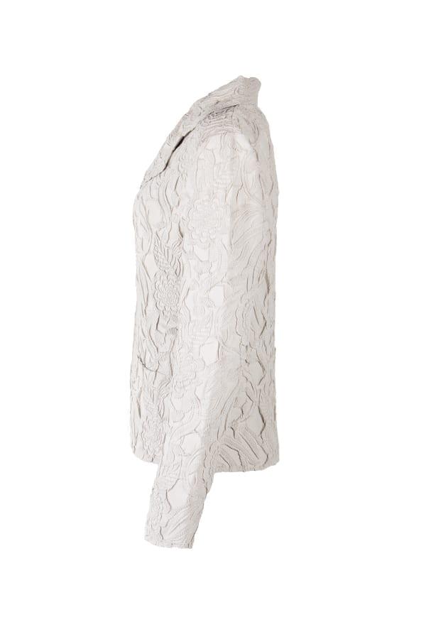 Kavaj Edelie i kittfärgad fuskmocka med unik design och spets-plissering. Runt den V-ringade halsen sitter en kavajkrage med slag.