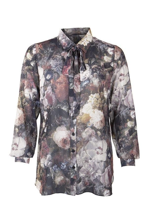 Blus Flora är en skjortblus med höstigt blomprint i mustiga färger av brunmulti och stone. Lång ärm med manchett och knapp nedtill.